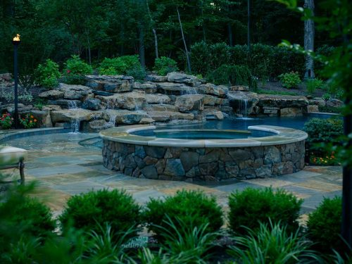 Custom pool and landscape architecture with waterfall and spa